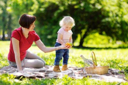 Photo pour Âgées de moyen belle femme et son adorable petit-fils peu avoir un pique-nique dans le parc ensoleillé - image libre de droit