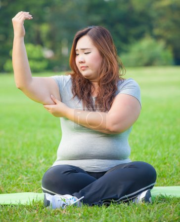 Photo for Young asian fat woman checking her arm fat - Royalty Free Image