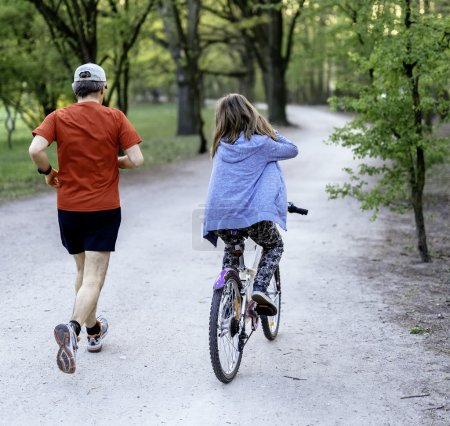 Photo for Dad with daughter on bike in the park - Royalty Free Image