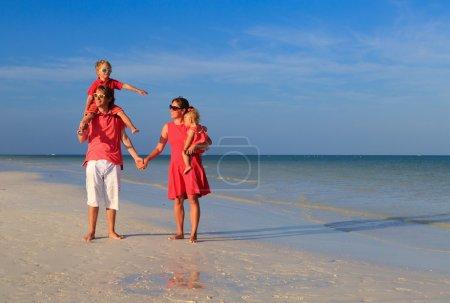 Photo pour Jeune famille avec deux enfants à pied à la plage de sable - image libre de droit