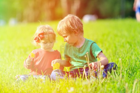 Two kids playing with dandelions on green grass