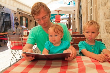 Father with kids in city cafe on summer day