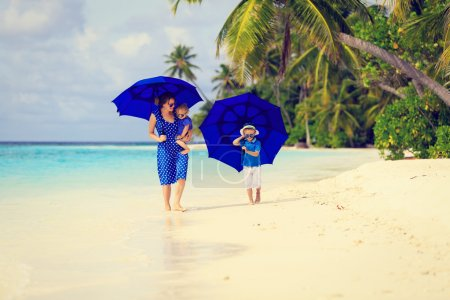 mother and two kids at beach with umbrellas