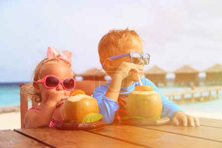 little boy and girl drinking coconut cocktail on tropical resort