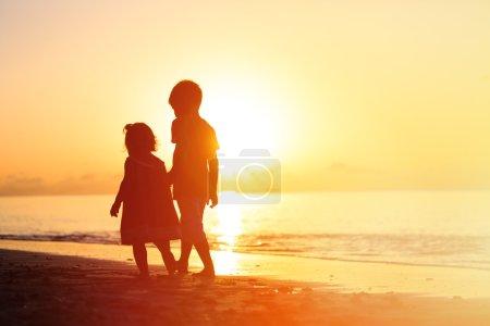 little boy and girl walking on sunset beach