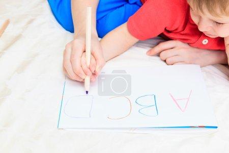 Photo pour Mains de la mère et de l'enfant lettres d'écriture, éducation précoce - image libre de droit