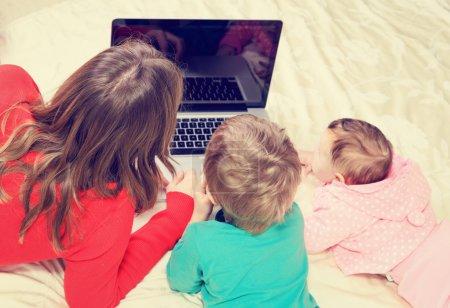 Photo pour Enseignant et les enfants qui regardent ordinateur portable, éducation des jeunes enfants et de la technologie - image libre de droit