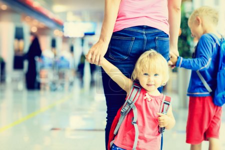mother and two kids walking in the airport