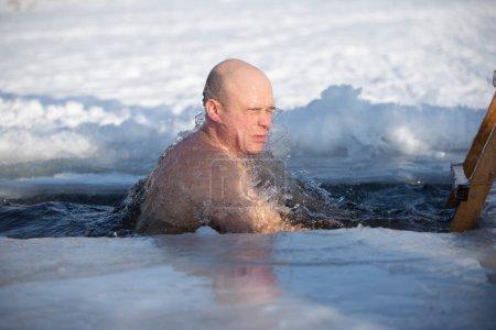 Photo pour Un homme plonge dans un trou de glace pendant la fête hivernale du baptême de Jésus. Un homme nage dans le trou de glace en hiver. Morses. - image libre de droit