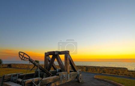 antique catapult by Alghero promenade at sunset