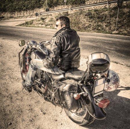 Photo pour Motard sur une moto classique à effet sépia ton - image libre de droit