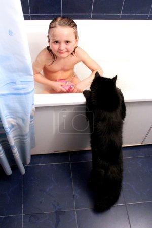 Photo pour Image de petite fille prenant un bain avec curieux chat noir - image libre de droit