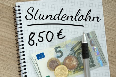 Foto de Writing pad with money and the german words hourly wage - Imagen libre de derechos