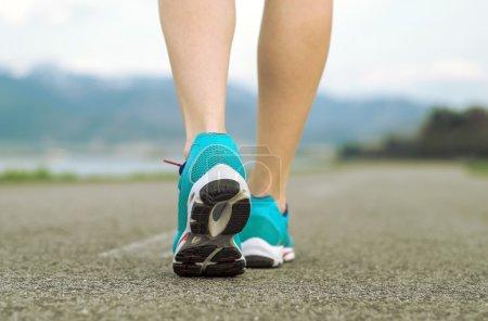 Runner athlete feet running on road under sunlight...