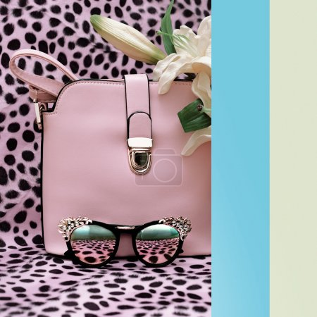 Handbags and fashion stylish sunglasses on leopard print backgro