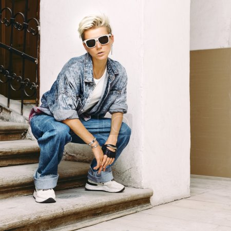 blonde in a stylish denim clothing. Street fashion