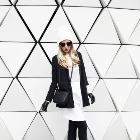 Glamorous blonde standing at the wall. Urban fashion black and w