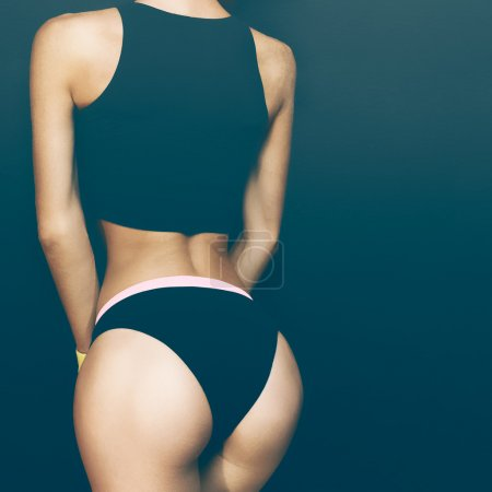 Slim athletic fitness blonde on a black background in the fashio