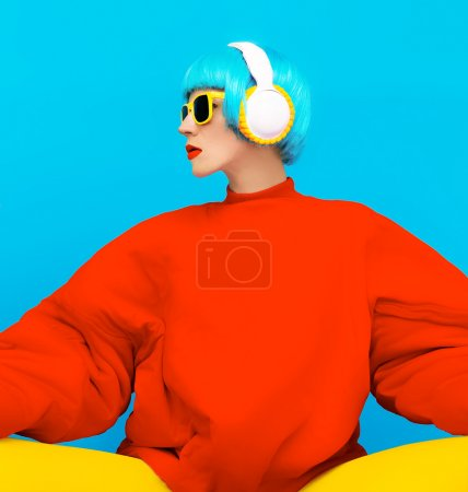Glamorous fashion lady in bright clothes listening to music. All