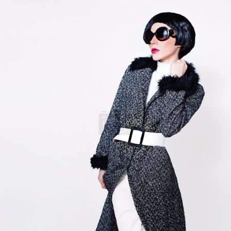 Lady in stylish sunglasses and fashionable coat on a white backg