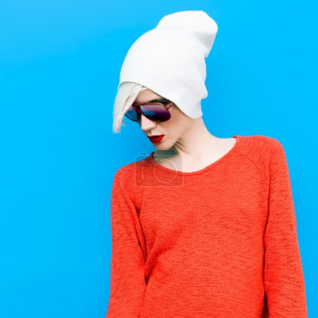 Photo for Fashion blond girl with trendy cap and sunglasses on a blue background - Royalty Free Image