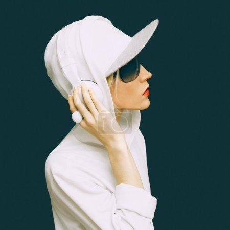 Photo pour DJ fille en vêtements blancs sport écouter de la musique sur fond noir. Style de mode urbaine - image libre de droit