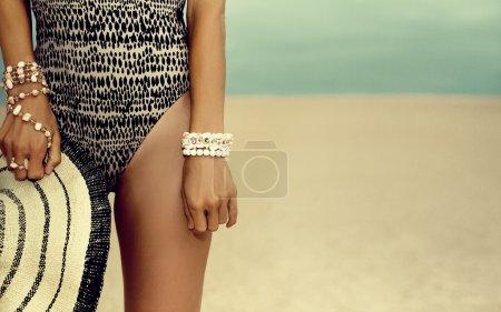 glamouröses braungebranntes Model in modischem Badeanzug und stylischem Accessoire