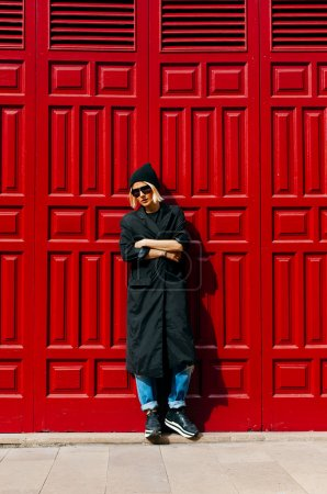 Stylish girl at the red door .Urban fashion style