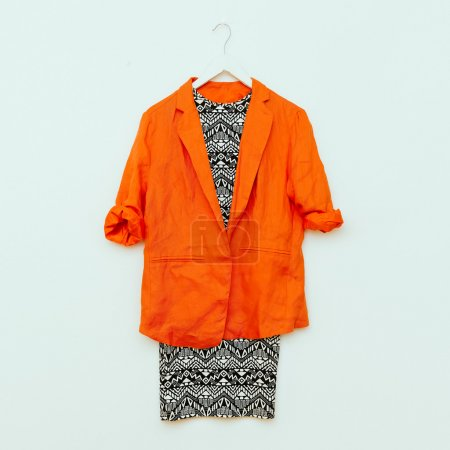 Dress with geometric prints and orange jacket. Trendy Look