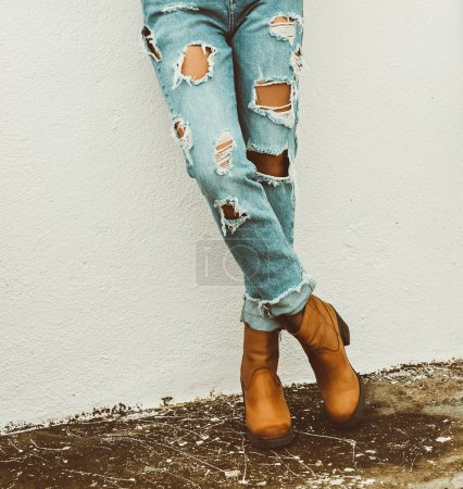 Fashionable lady Style. Torn jeans and boots
