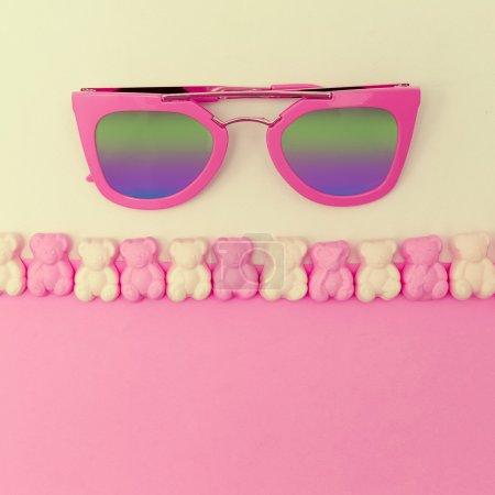Stylish pink sunglasses on sweet background. Vanilla minimalism