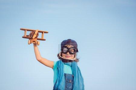 Photo pour Enfant heureux jouant avec un avion jouet sur fond de ciel d'été. Concept de voyage - image libre de droit