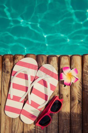 Photo for Flip-flops on wood against blue water background. Summer vacation concept - Royalty Free Image