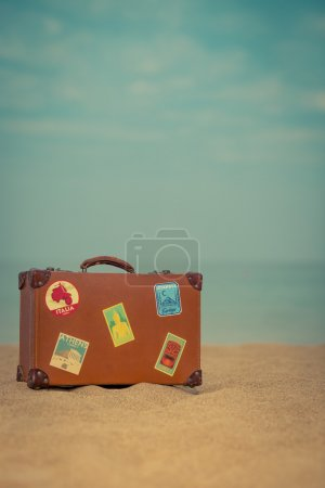 Photo for Vintage suitcase on sandy beach against blue sea and sky background. Summer vacation and travel concept - Royalty Free Image