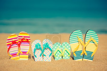 Photo for Flip-flops on sandy beach against blue sea background - Royalty Free Image