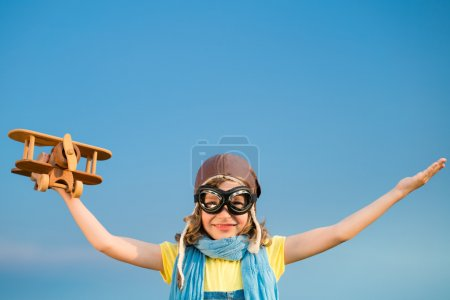 Photo pour Joyeux enfant jouant avec jouet avion à l'extérieur. Le gamin s'amuse sur fond de ciel d'été. Concept voyage et imagination - image libre de droit