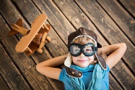 Photo pour Child pilot with vintage plane toy on grunge wooden background - image libre de droit