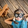 Child pilot with vintage plane toy on grunge woode...