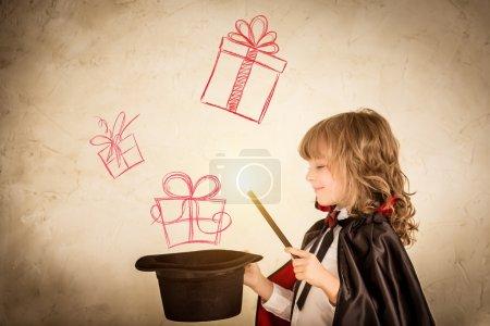 Photo pour Enfant magicien tenant un chapeau haut de forme avec des boîtes-cadeaux dessinées. Concept de vacances de Noël - image libre de droit