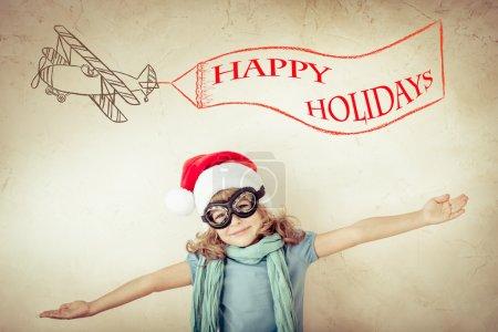 Photo pour Joyeux enfant dans le chapeau du Père Noël jouant avec un avion jouet à la maison. Rétro tonique - image libre de droit