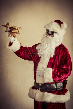 Photo for Santa Claus holding vintage wooden airplane against grunge wall background. Xmas holiday concept - Royalty Free Image