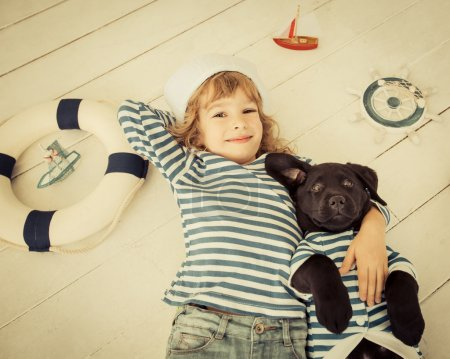 Photo pour Heureux enfant habillé en marin. Enfant jouant avec le chien à la maison. Notion de voyage et d'aventure - image libre de droit