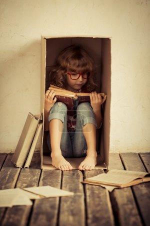 Photo pour Enfant assis dans une boîte en carton. Un livre de lecture pour enfants. Concept de liberté et d'imagination - image libre de droit