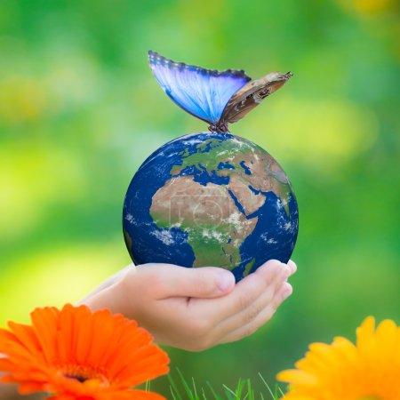 Photo pour Planète de terre retenant d'enfant avec le papillon bleu dans des mains contre le fond vert de ressort. Éléments de cette image fournis par la Nasa - image libre de droit
