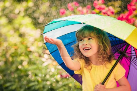 Photo for Happy child in the rain. Funny kid playing outdoors in spring park - Royalty Free Image