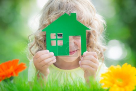 Foto de Happy child holding house in hands against spring green background. Real estate business concept - Imagen libre de derechos