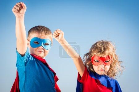 Photo pour Enfants super héros s'amuser sur fond de ciel d'été - image libre de droit