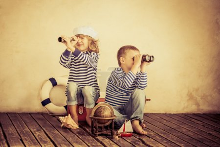 Photo for Children playing with vintage nautical things having fun at home, travel and adventure concept - Royalty Free Image