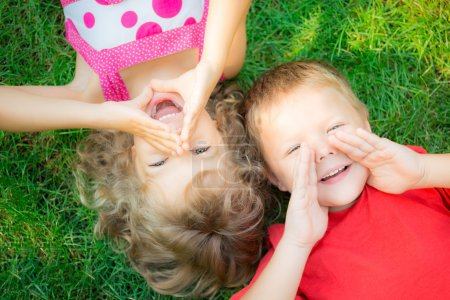 Photo for Funny kids shouting outdoors. Happy children lying on green grass. Communication concept - Royalty Free Image
