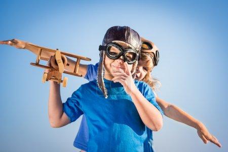 Photo pour Enfants heureux jouant avec un avion en bois vintage. Portrait d'enfants sur fond de ciel d'été - image libre de droit